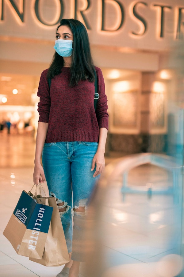 Shopaholic Woman with shopping bag outside Nordstroms with a mask pandemic shopping Ranjani Rao